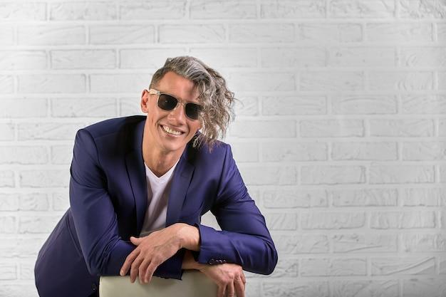 Modieuze zakenman die met krullend lang haar in zonnebril op stoel op wit zitten