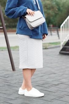 Modieuze zomeroutfit, een meisje in een sweater en witte sneakers met tas