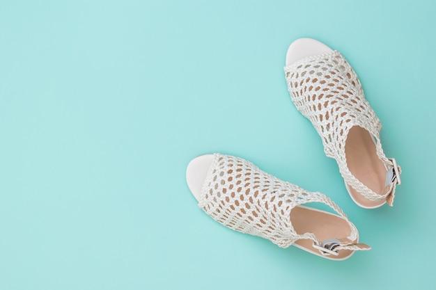 Modieuze zomerschoenen van wit echt leer op een blauwe ondergrond