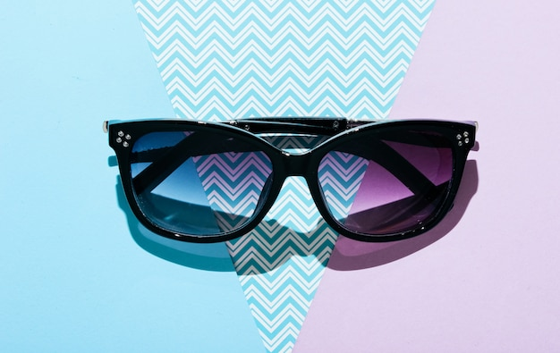 Modieuze zonnebril op een creatieve pasteltafel. bovenaanzicht