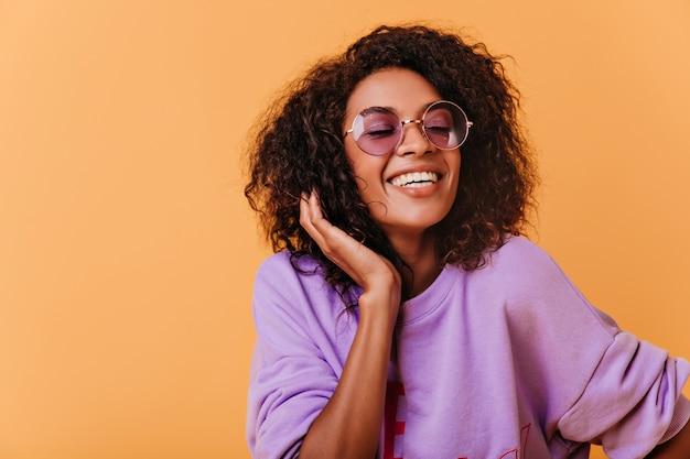 Modieuze zwarte die zich voordeed op kleurrijk met vrolijke glimlach. optimistisch afrikaans meisje in paarse trui