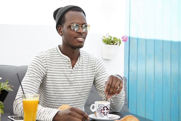 Modieuze zwarte man in ronde zonnebril, gestreept overhemd en hoofddeksel rustend op het terras, genietend van koffie, vrolijk kijkend, ontspannen en zorgeloos tijdens reis in het buitenland