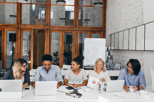 Moe aziatische it-specialist koffie drinken en kijken naar vrouwelijke collega die met laptop werkt. indoor portret van jonge mensen uit het bedrijfsleven zitten samen aan de tafel in de conferentiezaal.