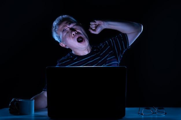 Moe aziatische man van middelbare leeftijd die geeuwt terwijl hij 's nachts op zijn computer in zijn kantoor aan huis werkt
