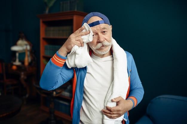 Moe bejaarde sportman in uniform na training thuis. volwassen mannelijke persoon op fitnesstraining binnenshuis