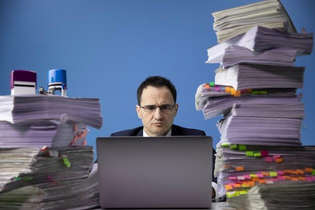 Moe bezorgd zakenman achter bureau met enorme stapel documenten