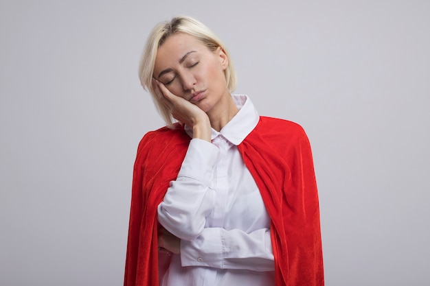 Moe blonde superheld vrouw van middelbare leeftijd in rode cape hand op gezicht met gesloten ogen geïsoleerd op een witte muur met kopie ruimte