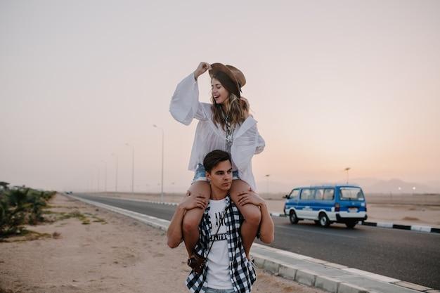 Moe brunette man in geruite overhemd draagt zijn vriendin op zijn schouders kijken naar zonsondergang. vrolijke jonge vrouw in trendy hoed met plezier met vriendje op buiten avond date