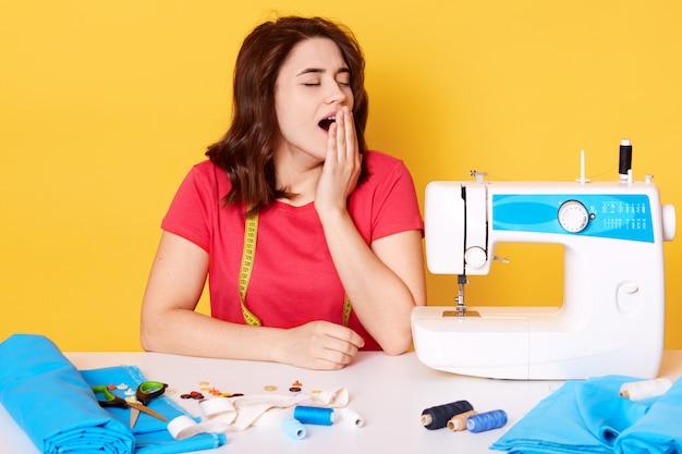 Moe drukke naaister zit aan tafel met naaimachine