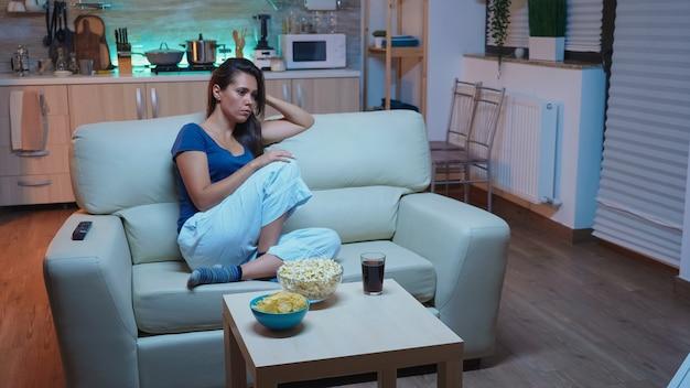 Moe eenzame vrouw slapen op de bank in de woonkamer tijdens het kijken naar film. uitgeputte slaperige jonge dame in pyjama die in slaap valt op de bank voor de televisie en 's nachts de ogen sluit in de woonkamer.