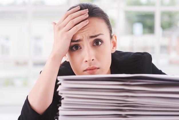 Moe en overwerkt. depressieve jonge vrouw in pak kijkt uit de stapel documenten die op tafel liggen en raakt haar voorhoofd met de hand aan