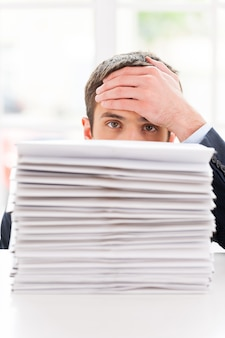 Moe en overwerkt. depressieve jongeman in overhemd en stropdas die uit de stapel documenten kijkt die op tafel liggen en zijn voorhoofd met de hand aanraakt
