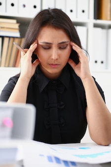 Moe en uitgeputte vrouw kijkt naar documenten die haar hoofd met haar handen ondersteunen