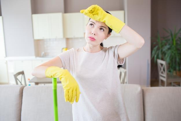 Moe en uitgeputte vrouw staat in het midden van de kamer en houdt linkerhand op het voorhoofd. ze draagt gele handschoenen. het meisje leunt aan groene stok met een andere hand.