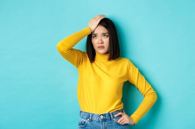 Moe en verdrietig aziatische vrouw facepalm, zuchtend en verdrietig opkijkend, zich onrustig voelen terwijl ze tegen een blauwe achtergrond staat.