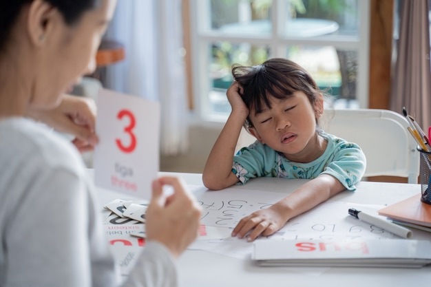 Moe en verveeld peuter tijdens het studeren met moeder