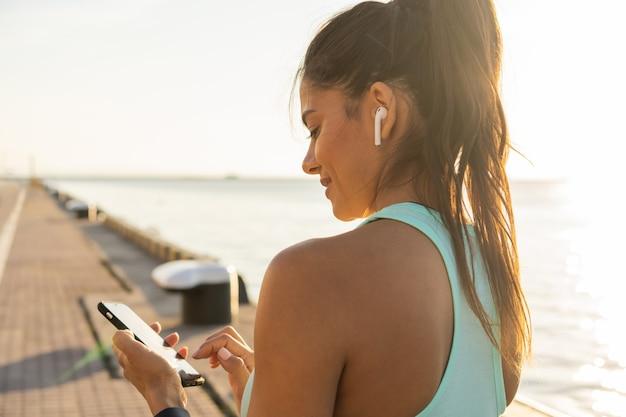 Moe fitness vrouw zweten een pauze nemen van het luisteren naar muziek op de telefoon na een zware training. jonge vrouw die naar muziek luistert met oortelefoons op smartphone-app voor fitnessmotivatie