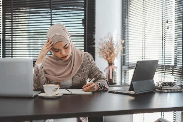 Moe gefrustreerd jonge moslim zakenvrouw bruine hijab gevoel benadrukt hoofd met handen te houden