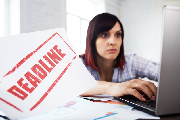 Moe gestoorde vrouwelijke werknemer met hoofdpijn. gestemde vrouw in kantoor hoofd in handen houden en na te denken over de deadline