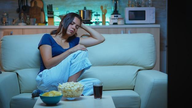 Moe huisvrouw in slaap vallen voor tv zittend op een gezellige bank in de woonkamer. uitgeputte eenzame slaperige verveelde vrouw in pyjama die op de bank slaapt terwijl ze 's avonds laat alleen thuis televisie kijkt