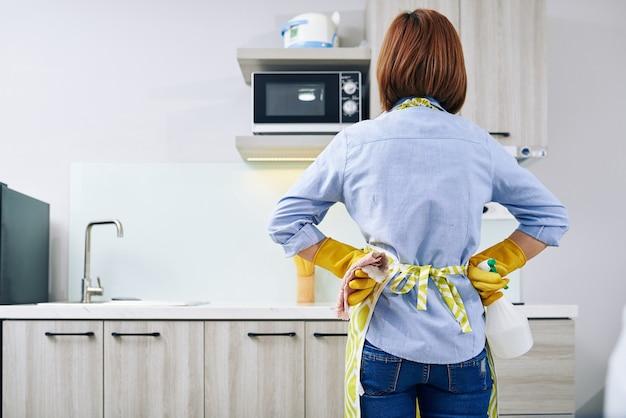 Moe huisvrouw met schoonmaakspray en microfiber handdoek kijken naar aanrecht, uitzicht vanaf de achterkant