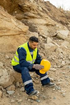 Moe ingenieur in uniform met rust op de bouwplaats