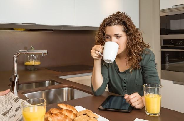 Moe jong meisje met kopje koffie in een ontbijt