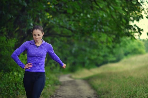Moe jong meisje op een run in het bos. buitensport