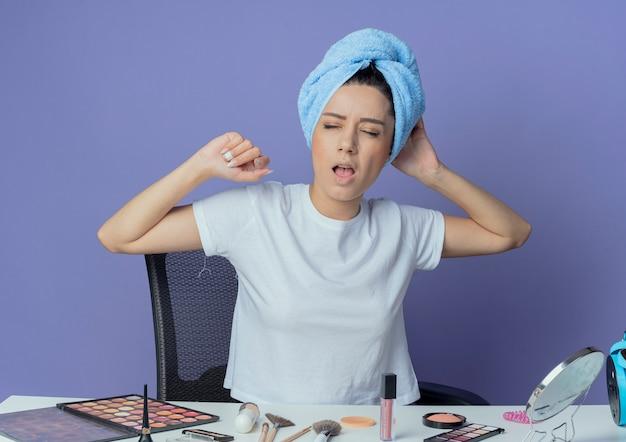 Moe jong mooi meisje zittend aan make-up tafel met make-up tools en met badhanddoek op hoofd geeuwen met gesloten ogen en hoofd aanraken en hand in de lucht houden