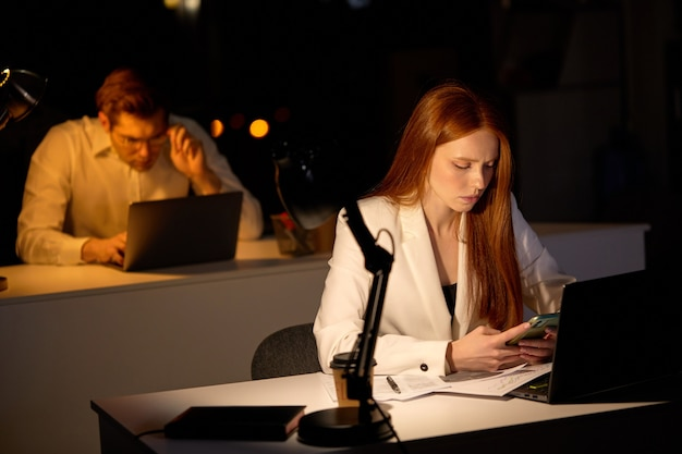 Moe jonge blanke vrouw die 's avonds laat op kantoor werkt en er slaperig uitziet, smartphone gebruikt, wat rust nodig heeft, overwerk overbelasting deadline werkconcept. ruimte kopiëren. focus op roodharige dame