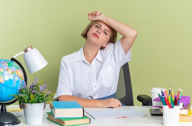 Moe jonge blonde student meisje zit aan bureau met school tools kijken camera houden arm op voorhoofd geïsoleerd op olijf groene muur