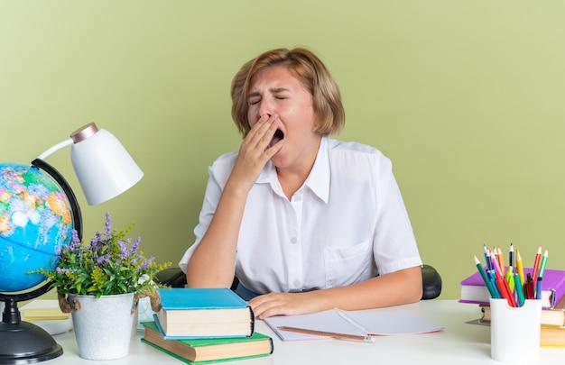 Moe jonge blonde student meisje zit aan bureau met schoolgereedschap geeuwen met gesloten ogen geïsoleerd op olijfgroene muur