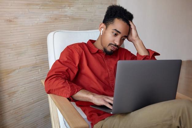 Moe jonge gekrulde donkere man met baard die zijn hoofd met de hand vasthoudt terwijl hij aandachtig kijkt op het scherm van zijn laptop, zittend in een stoel op het interieur