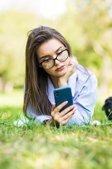 Moe jonge hipster meisje met behulp van slimme telefoon liggend op het gras in het park