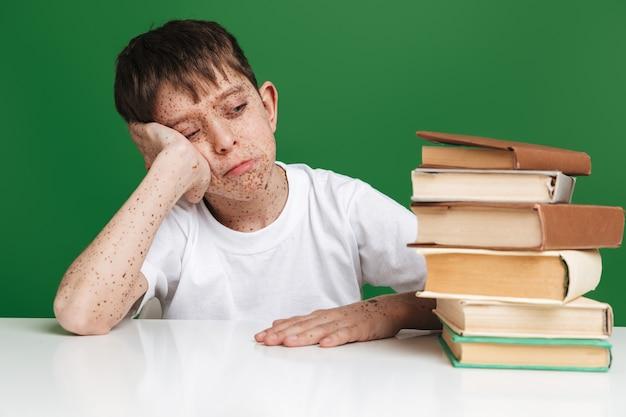 Moe jonge jongen met sproeten slapen terwijl hij bij de tafel zit met boeken over groene muur