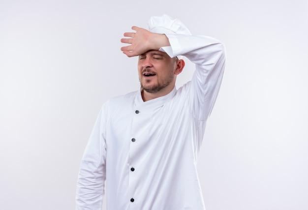 Moe jonge knappe kok in uniform chef-kok hand zetten voorhoofd en geeuwen met gesloten ogen geïsoleerd op witte ruimte