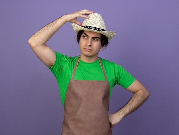 Moe jonge mannelijke tuinman in uniform dragen tuinieren hoed hand zetten hoed