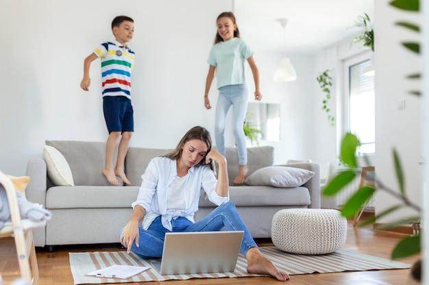 Moe jonge moeder zittend op de vloer en werken met laptop en documenten terwijl kleine kinderen en springen op de bank en plezier maken en lawaai maken