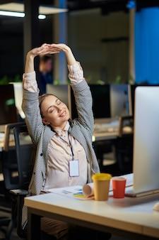 Moe jonge vrouw werkt in nachtkantoor. slaperige vrouwelijke zakenvrouw, donker zakencentrum interieur, moderne werkplek