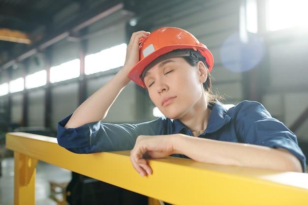 Moe jonge vrouwelijke ingenieur in werkkleding en veiligheidshelm dutten terwijl leunend door bar midden in de werkdag