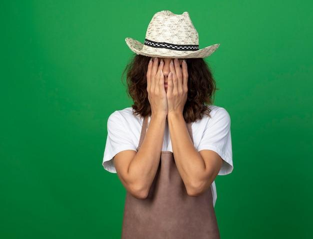 Moe jonge vrouwelijke tuinman in uniform dragen tuinieren hoed bedekt gezicht met handen