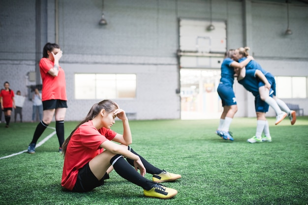 Moe jonge vrouwelijke voetballer in sport uniforme zittend op groen veld van andere meisjes rusten na de wedstrijd