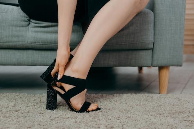 Moe jonge zakenvrouw in zwarte jurk zittend op de bank en schoenen close-up opstijgen