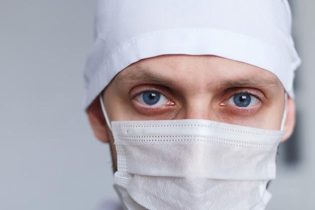 Moe jongeman arts in masker tijdens coronavirus. dramatisch portret van dokter, close-up