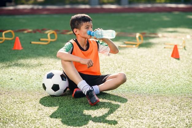 Moe jongen in voetbal uniform drinkt water uit de plastic fles na de training