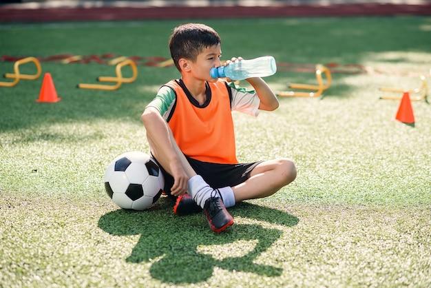 Moe jongen in voetbal uniforme drankjes met water na intensieve training