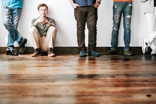 Moe jongen zittend op een houten vloer