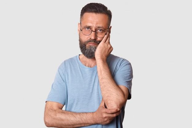 Moe kalm man staande geïsoleerd op wit, zijn gezicht aan te raken met een hand, diep van streek, het dragen van t-shirt en trendy bril.