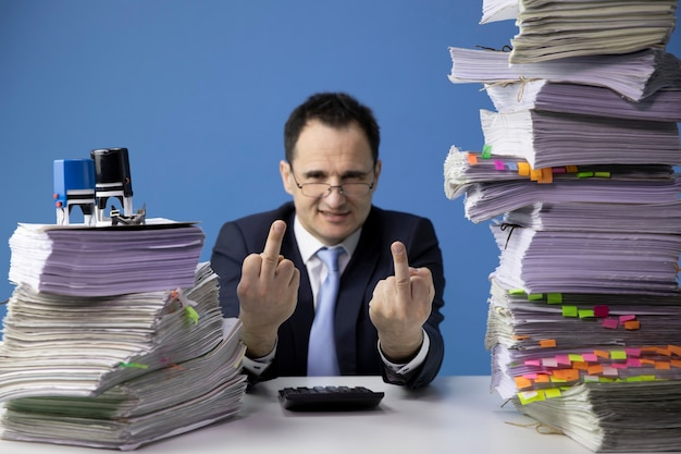 Moe kantoormedewerker doet middelvinger teken, zittend aan een bureau met enorme stapel documenten
