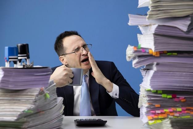 Moe kantoormedewerker gaapt moe zittend aan een bureau met een enorme stapel documenten